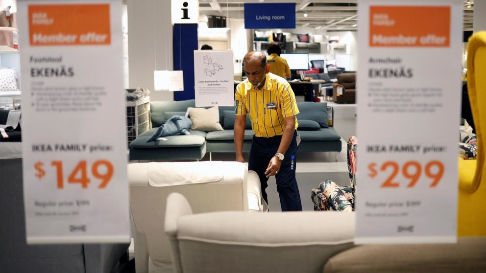 A worker at an Ikea store is preparing to lift a sofa.