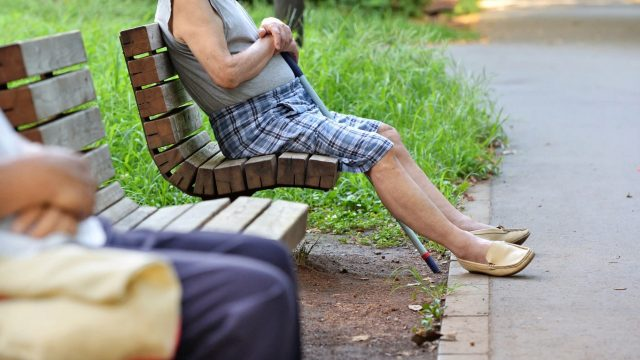 Image of a pair of elderly people sitting on a pair of benches in a park, far apart from each other.