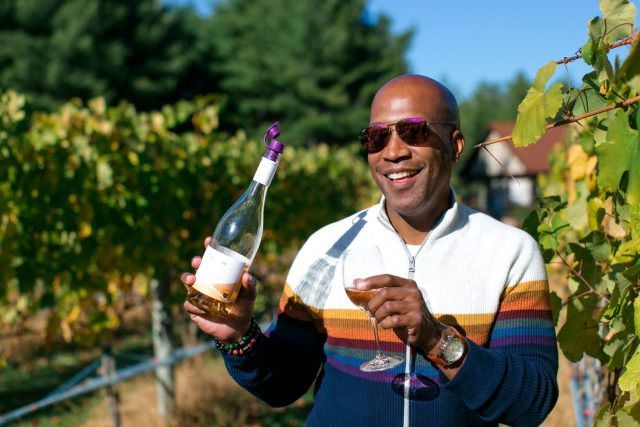 Person pouring white wine from the bottle to a glass in the middle of a vineyard.