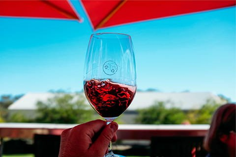 Glass of red wine contrasted with the intense blue of the sky.