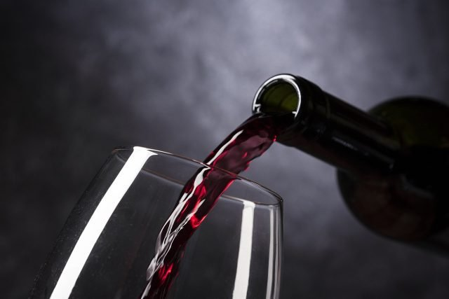 Bottle of red wine emptying its contents into a glass.